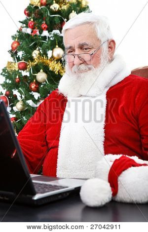 Santa Claus with real beard using laptop, Christmas tree in background