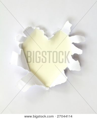 Sheet of paper with a Heart shape hole against bright white background isolated on white