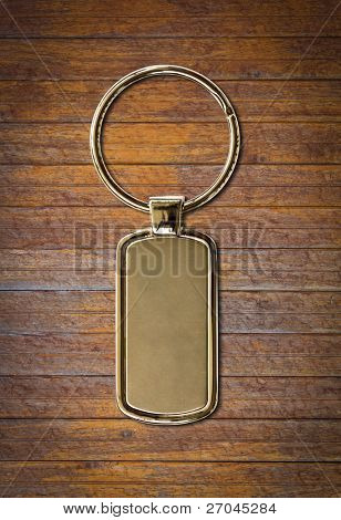 Metal key chain as a frame with space for text or illustrations on wood wall