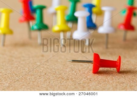 Group of colorful push pins on cork bulletin board.