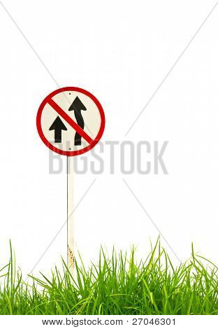 Traffic sign and fresh spring green grass isolated on white background