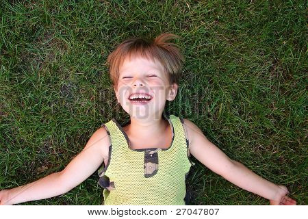 Baby laughing, lying on the grass