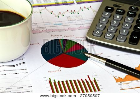 Various financial charts on the table with  calculator, coffee and pen
