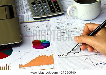Hand write on Various financial charts on the table with laptop, calculator and  coffee