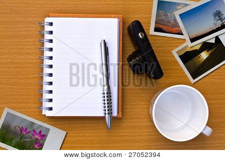 Note book , photo , pen, coffee cup and camera. On the floor of the wooden table.