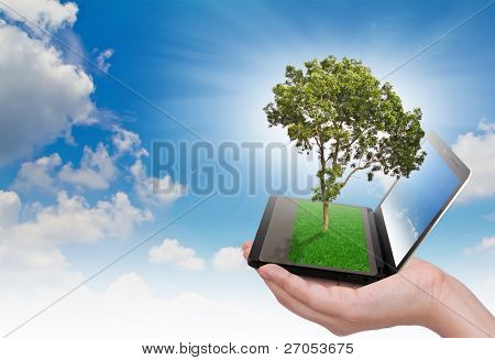 Human hand holding notebook and tree with grass on keypad