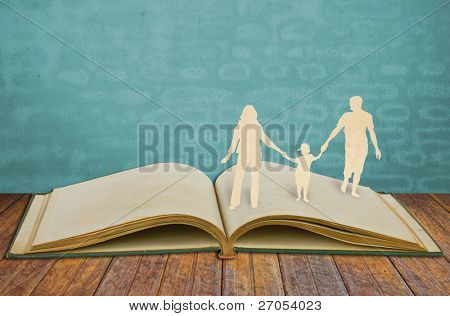 Paper cut family symbol on old book