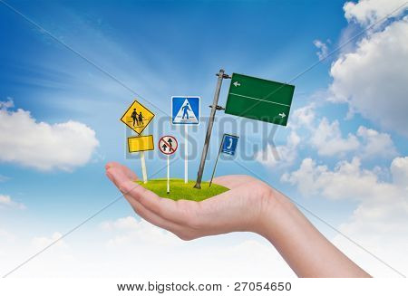 Road sign in hand over blue sky