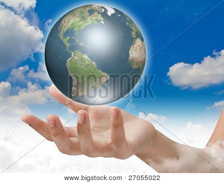 Eco concept : Earth in hands over blue sky