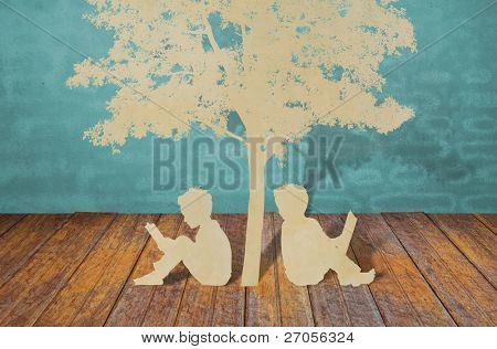 Paper cut of children read a book under tree