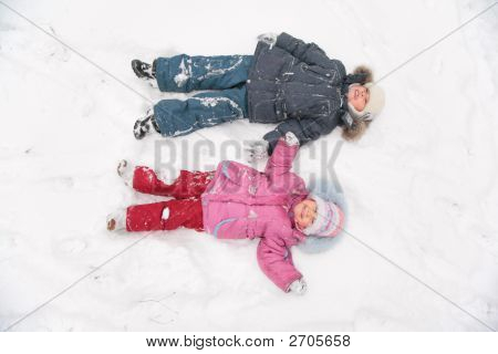 Two Children Lie On Snow