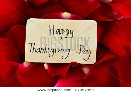 "Red rose petals and old card with word "" Happy Thanksgiving Day  """