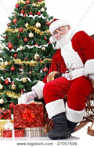 Santa sitting next Christmas tree and taking milk  , that were left  for him