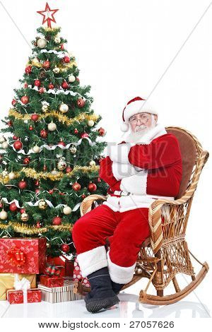 Santa Claus sitting in rocking chair next full decorated Christmas tree, isolated on white background