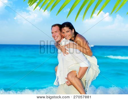 couple in love piggyback playing in a beach at blue Mediterranean [ photo-illustration]