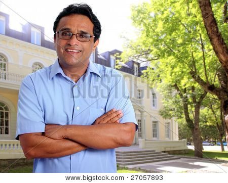 Indian latin man as hotel owner or real estate businessman smiling in front of house facade