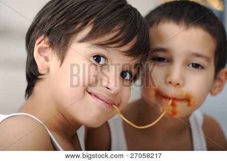 Two little boys eating spaghetti