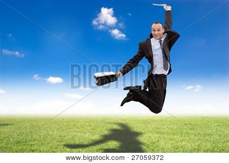 happy businessman jumping in green meadow with shadow on grass under blue sky