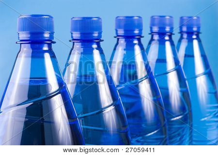 five blue water plastic bottles aligned, focus on the first one