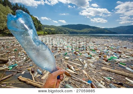hand throwing plastic bottle in beautiful landscape ruined by pollution, bicaz lake, romania
