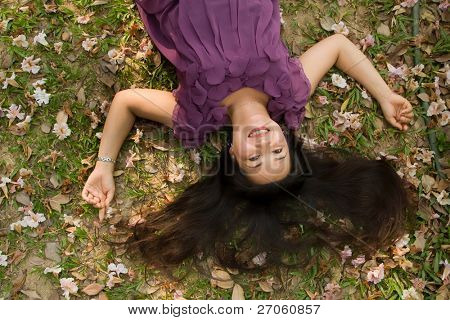 happy asian woman lying on grass and smiling
