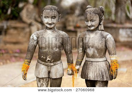 stone religious sculpture of couple holding hands, thailand
