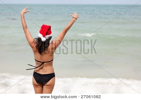 beautiful woman wearing santa claus cap raising arms at tropical beach