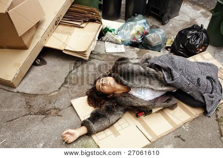 poor young drunk woman lying in trash in city street