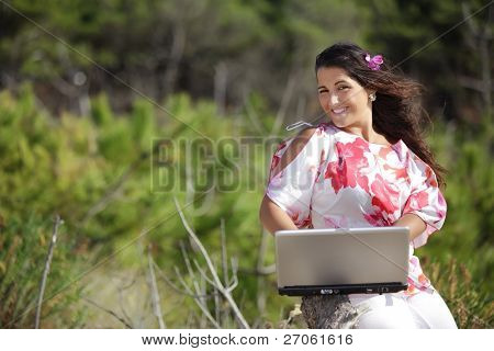 young woman using laptop in wild pine tree forest