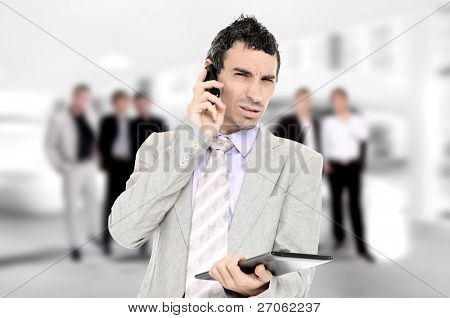 Young businessman holding a tablet his hands and business team at the office