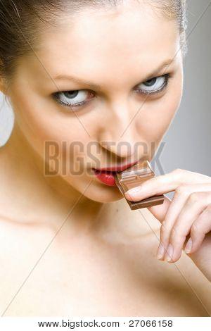 closeup of female face biting a milk chocolate