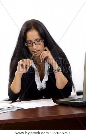 Businesswoman reading papers at her desk over white background