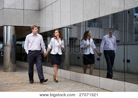 Romantic Couple On Walk Along Mirror Of Modern Building
