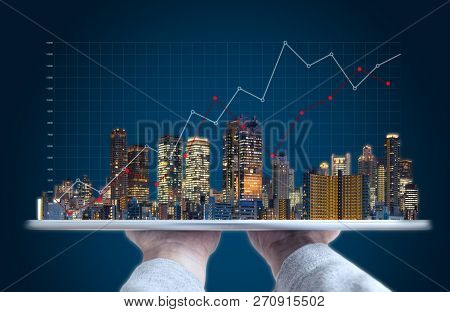 poster of Real Estate Business Investment And Building Technology. Hand Holding Digital Tablet With Buildings