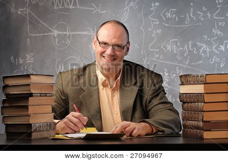 Smiling teacher surrounded by books in a classroom