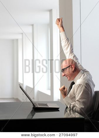 Triumphing businessman in front of a laptop