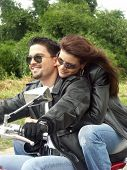 Couple enjoying a ride by motorcycle.