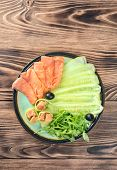 Plate With Sliced Pieces Of Red Salmon Fish, Cucumber Slices, Arugula Olives And Rolls On Wooden Tab poster