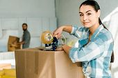 Wife Packing Cardboard Box With Scotch Tape And Husband Behind, Moving Concept poster