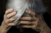picture of elderly woman  - elderly woman holding head with wrinkled hands during time of grief and sadness - JPG