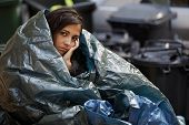 stock photo of tramp  - poor homeless young woman wrapped in plastic tarpaulin - JPG