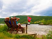 Mature Couple Woman And Man Relaxing Outdoor, Sitting On Wooden Chairs On Lake Fjord Shore. Holidays poster