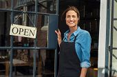 Portrait of a happy waitress standing at restaurant entrance. Portrait of mature business womanatten poster