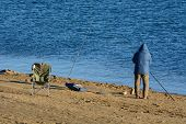 Unrecognizable Fisherman Fishing Alone Dressed In Winter Unrecognizable Fisherman In Winter Parka Wi poster