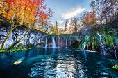 Amazing waterfall with pure blue water in Plitvice lakes. Orange autumn forest on background. Plitvi poster