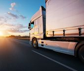 Loaded European truck on motorway in beautiful sunset light. On the road transportation and cargo. poster