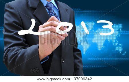 businessman hand writing 2013 on world map