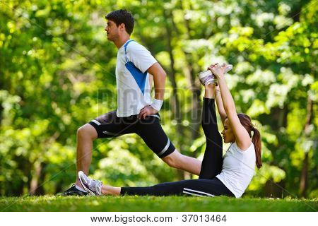 young health couple doing stretching exercise relaxing and warm up after jogging and running in park