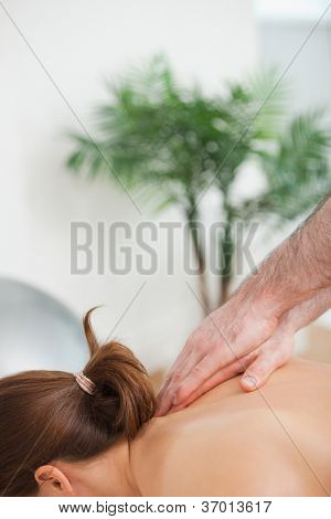 Practitioner massaging the top of back of his patient indoors
