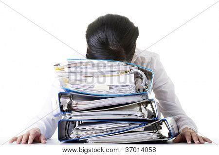 Mujer triste con ringbinders sentado en el escritorio. Cansado y mujer de negocios de exhousted.